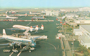 Photo of United DC-7 and TWA Lockheed L-1049 (Constellation) parked next to each other at LAX